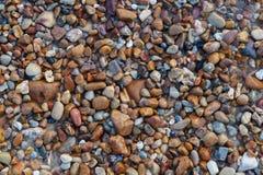 Natuurlijk rond gemaakte grint op zee kust, van het achtergrond aardstrand textuur Stock Afbeeldingen