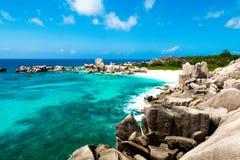 Natuurlijk tropisch en geïsoleerd strand met grote rotsen, met zand e stock foto's