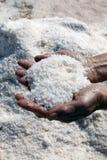 Natuurlijk zout in donkere handen van het werken Stock Afbeelding