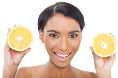 Natuurlijke aantrekkelijke modelholdingsplakken van sinaasappel in beide handen Stock Foto's