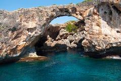 Natuurlijke boog en de grot in Cala Antena Stock Afbeelding