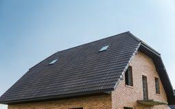 Natuurlijke bruine daktegels op een gebouw tegen blauwe hemel stock afbeeldingen