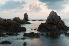Natuurlijke gebroken rots op het strand met de achtergrond van de zonsonderganghemel Royalty-vrije Stock Fotografie