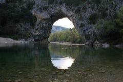 Natuurlijke gevormde brug van stenen en rotsen over een rivier stock afbeelding