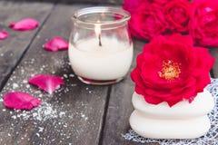 Natuurlijke kosmetische zeep met rode rozen en een hete kaars op een donkere houten achtergrond stock foto