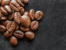 Natuurlijke middel geroosterde koffiebonen op een gekraste zwarte backgro stock fotografie