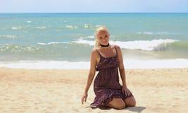 Natuurlijke mooie de golvenachtergrond van de vrouwenzitting op het strand royalty-vrije stock foto's