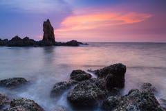 Natuurlijke rots over zeekust met de achtergrond van de zonsonderganghemel Stock Foto's