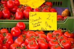 Natuurlijke tomaten in dozen op de markt van de landbouwer Stock Foto