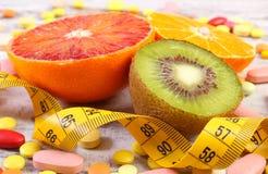 Natuurlijke vruchten, centimeter en medische pillen, vermageringsdieet, keus tussen gezonde voeding en medische supplementen stock foto's