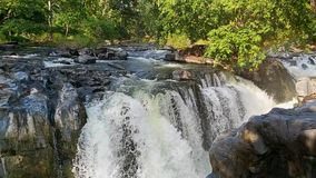 Natuurlijke waterval door de harde bruine rots in een plattelandswildernis in een mooie zonnige dag stock video