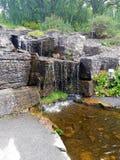 Natuurlijke waterval in Oslo, rand door installaties en bomen De stoom lijkt eronder brons in kleur stock foto