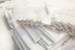 Natuurlijke witte stoffen voor beddegoed en kant dat als ventilator wordt gestapeld royalty-vrije stock fotografie