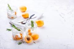 Natuurlijke yoghurt met stukken van abrikozen en rozemarijn stock foto
