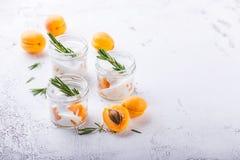 Natuurlijke yoghurt met stukken van abrikozen en rozemarijn royalty-vrije stock afbeeldingen