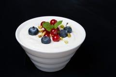 Natuurlijke yoghurt met verse bessen op een zwarte achtergrond Royalty-vrije Stock Foto's
