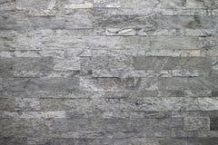 Natuursteen, vlot lineair metselwerk, grijze hulptextuur De muur wordt gemaakt van steen, is de oppervlakte geweven stock afbeelding