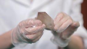 Natuursteenamethist of een ander mineraal, steen Het wilde amethist in wijfje dient witte handschoenen in Rotssteen in handen Stock Foto's
