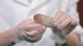 Natuursteenamethist of een ander mineraal, steen Het wilde amethist in wijfje dient witte handschoenen in Rotssteen in handen royalty-vrije stock afbeelding