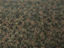 Natuursteengraniet van zwart-bruine kleur met donkere kastanjebruine impregnaties stock afbeeldingen