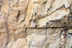 Natuursteenhulp, rode kleur Achtergrondrots met een grijze textuur met kleine barsten Doorstane steenlagen van verschillend stock foto