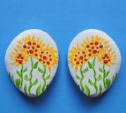 Natuurstenen met geschilderde bloemen stock fotografie
