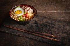 Natychmiastowy kluski z wieprzowiną, jajkiem i warzywami na czarnym pucharze na drewno stole tam, jest chopstick umieszczającym p zdjęcie stock