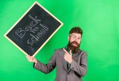 Nauczania zajęcie żąda talent i doświadczenie Nauczyciel wita uczni podczas gdy chwyta chalkboard inskrypcja z powrotem obrazy stock