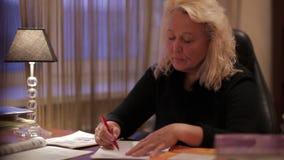 Nauczyciel angielskiego siedzi przy stołem pisze coś. zbiory wideo