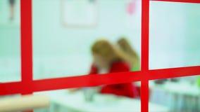 Nauczyciel angielskiego uczy się w klasie Kamera usuwa przez szkła przy Angielskiej klasy drzwiami Dorosli ucznie słuchają zbiory