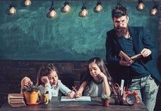 Nauczyciel czytelnicza ksi??ka z dzieciakami w bibliotece zdjęcia royalty free
