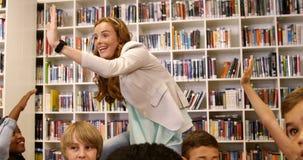 Nauczyciel daje wysokości pięć dzieciaki w bibliotece zbiory wideo