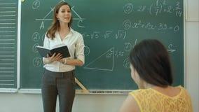 Nauczyciel, docent lub pedagog daje podczas gdy lekcja przed blackboard lub wsiadamy prześcieradło papier i kształcimy lub zdjęcie wideo