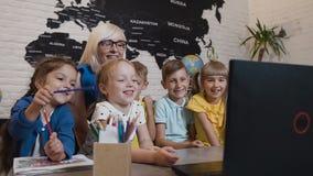 Nauczyciel dyskutuje program komputerowego z zabawy grupą ucznie Młoda kobieta z uczniami używa laptopów studia zdjęcie wideo