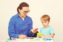 Nauczyciel i śliczna chłopiec ma zabawę, bawić się logiczną grę Dzieciak z nauczyciela uczenie przy preschool salą lekcyjną Naucz obrazy stock