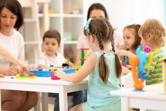 Nauczyciel i asystent bawić się z dziećmi w dziecinu zdjęcia royalty free