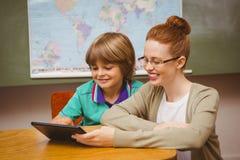 Nauczyciel i chłopiec używa cyfrową pastylkę w sala lekcyjnej fotografia royalty free