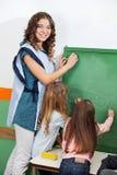 Nauczyciel I dzieci Pisze Na Chalkboard Zdjęcia Royalty Free