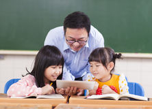 Nauczyciel i dzieci z cyfrową pastylką lub ipad Zdjęcie Royalty Free