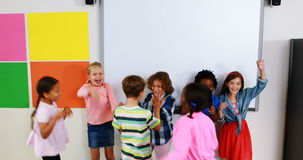 Nauczyciel i dzieciaki daje wysokości pięć w sala lekcyjnej zbiory