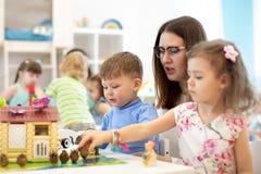 Nauczyciel i grupa dzieciaki buiding zabawka dom z konstruktorem w rzemiosło klasie obrazy royalty free