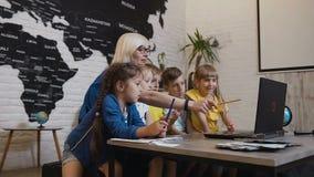 Nauczyciel i grupa podstawowi ucznie pracuje z laptopem i wtedy bierze selfie wpólnie Nauczyciel z zbiory wideo