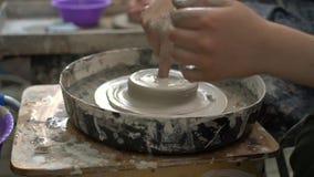 Nauczyciel i uczeń robi ceramicznemu pucharowi z palcem na ceramicznym toczymy wewnątrz warsztat zbiory wideo