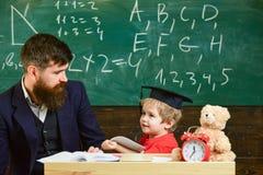 Nauczyciel i uczeń w mortarboard, chalkboard na tle Żartuje szczęśliwych studia z nauczycielem pojedynczo, w domu obrazy stock