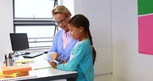 Nauczyciel i uczennica używa cyfrową pastylkę w bibliotece zbiory wideo