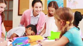 Nauczyciel i ucznie pracuje przy biurkiem wpólnie zdjęcie wideo