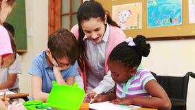 Nauczyciel i ucznie pracuje przy biurkiem wpólnie zbiory