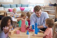 Nauczyciel I ucznie Pracuje Przy stołami W Montessori szkole Fotografia Royalty Free