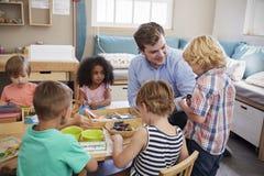 Nauczyciel I ucznie Pracuje Przy stołami W Montessori szkole Obrazy Royalty Free