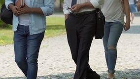Nauczyciel kontynuuje ciekawego wykład na kampusie podczas gdy chodzący z uczniami zbiory